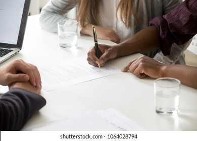 African american man puts signature on contract, interracial couple buying insurance or taking bank loan, making financial deal, family customers signing prenuptial agreement concept, close up view