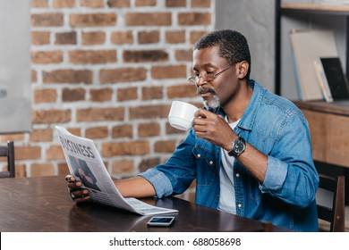 African american man reading newspaper and having coffee at table - Shutterstock ID 688058698