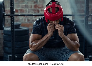 African american man in red boxing head gear putting gumshield. Determined boxer in sportswear sitting near boxing ring. Young man preparing for boxe practice with protective helmet.