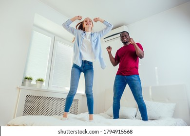 african american man and redhaired ginger woman laughing and jumping on bed at resort room