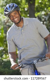 An African American man riding bicycle in the summer
