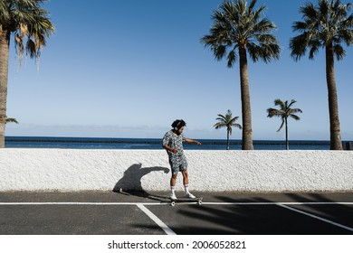 African american man riding longboard with beach in the background - Focus on face