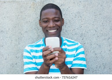 African american man sending text message
