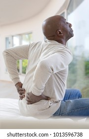 African American man with severe backache sitting on bed
