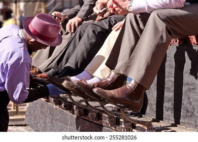 African American Man Shining Shoes in Financial District on Downtown City Street