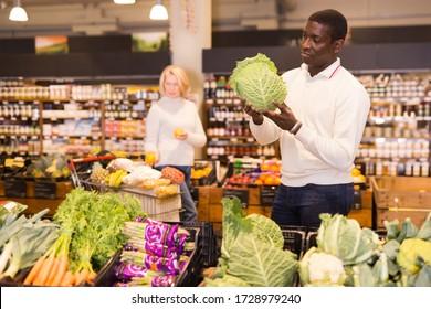 Afrikanisch-amerikanischer Mann kauft im Bio-Lebensmittelgeschäft Frischgemüse ein