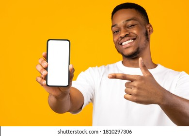 African American Man Showing Mobile Phone Screen Recommending App Smiling To Camera Posing Over Yellow Studio Background. Mockup