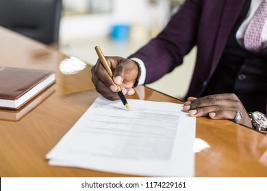 African american man signing contract, black man hand putting signature on official document, biracial clients customers couple make purchase or sign prenuptial agreement concept. clouse up