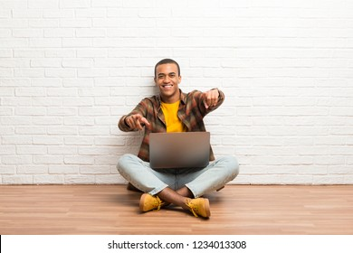 African american man sitting on the floor with his laptop points finger at you while smiling