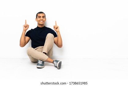 African American man sitting on the floor pointing up a great idea
