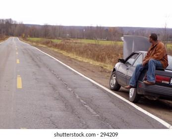 african american man sitting on broken down car
