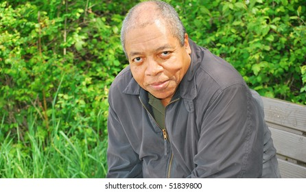 African american man sitting on a park bench.