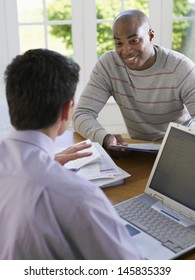 African American man sitting at table with financial advisor