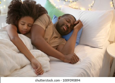 African American man sleeping with his daughter in bed. Family bedtime