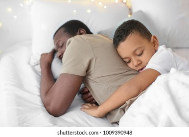 African American man sleeping with his son in bed. Family bedtime