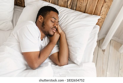 African American Man Sleeping Peacefully Resting With Eyes Closed Lying In Comfortable Bed In Bedroom At Home. Recreation, Healthy Male Sleep, Bedtime Napping Concept. Empty Space For Text