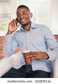 African american man smiling and talking on mobile phone while sitting on the chair in business office