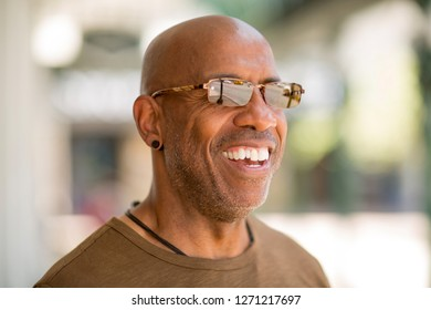African American man smiling wearing glasses.