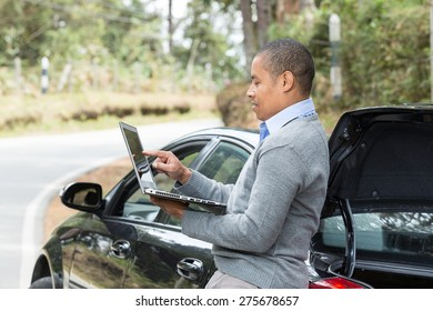 an African American man standing beside the car on the road pointing to the screen of your laptop