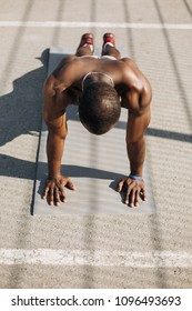 African American man stands on his arms on the ground doing push-ups during his morning exercises