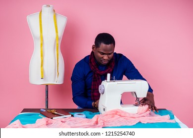 African American man tailor seamstress workshop stylish male model clothes designer the process of creating a new collection of wedding dresses on pink background in the studio copyspace
