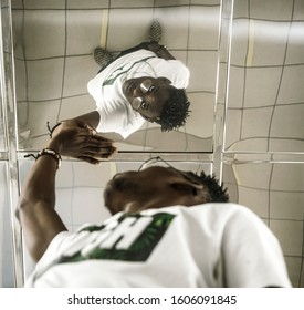 african american  man touching his reflection in the mirror ceiling. black male standing in narrow long corridor