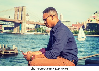 African American Man traveling in New York. Wearing blue shirt, brown pants, glasses, bracelets, a college student sitting at harbor, checking message on mobile phone. Boat, bridge on background.