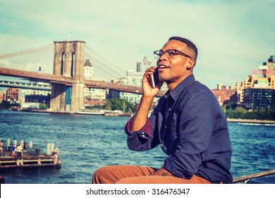 African American Man traveling in New York. Wearing blue shirt, brown pants, glasses, a college student sitting by East River, looking at sky, smiling, talking on phone. Brooklyn bridge on background.