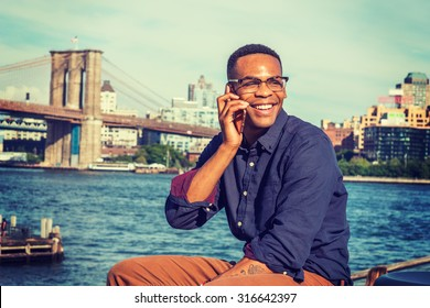 African American Man traveling in New York. Wearing blue shirt, brown pants, glasses, a college student sitting by East River, looking around, smiling, talking on phone. Brooklyn bridge on background.