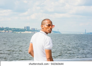 African American Man traveling in New York, wearing white Polo shirt, sunglasses, standing by Hudson River, turning around, looking back. Bridge, New Jersey on background. Color filtered effect
