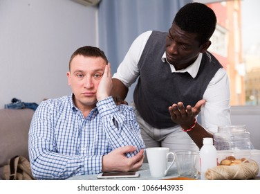 African American man trying to calm his friend and apologize after dispute