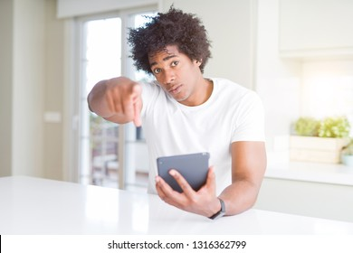 African American man using touchpad table pointing with finger to the camera and to you, hand sign, positive and confident gesture from the front