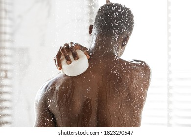 African American Man Washing Back With Sponge Taking Shower Standing Under Falling Water Drops In Modern Bathroom At Home. Men's Daily Hygiene And Male Bodycare Concept. Rear View