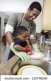 African American man washing dishes with son helping