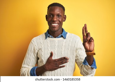 African american man wearing denim shirt and white sweater over isolated yellow background smiling swearing with hand on chest and fingers up, making a loyalty promise oath
