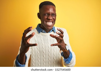 African american man wearing denim shirt and white sweater over isolated yellow background Shouting frustrated with rage, hands trying to strangle, yelling mad