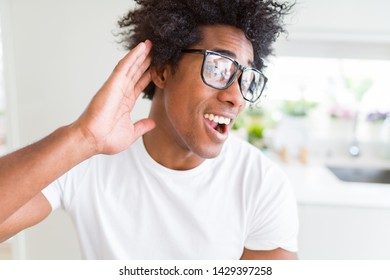 African American man wearing glasses smiling with hand over ear listening an hearing to rumor or gossip. Deafness concept.