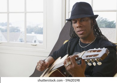 African American man wearing a hat and playing acoustic guitar