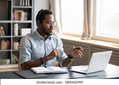 African American man wearing headphones speaking, using laptop, student wearing glasses learning language, watching video webinar or listening to lecture, mentor coach holding online lesson - Shutterstock ID 1805431999