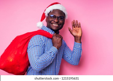 African American man wearing stylish plaid shirt great smile in santa hat with gift box on pink background studio.dark-skinned Santa Claus merry christmas with sack full of Christmas goodies
