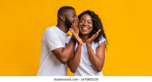 African American Man Whispering Gossips Into His Woman Ear, yellow studio background, panorama
