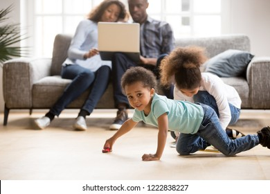 African American married couple using laptop together, sitting on couch at new home while children playing, toddler son playing with toy car on floor, little daughter drawing colorful pencil