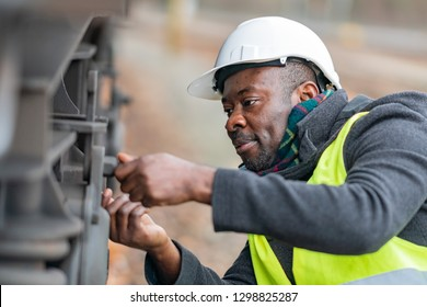 African American mechanic wearing safety equipment (helmet and jacket) checking and inspecting gear train