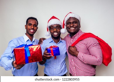 African American men in santa hat with gift box on white background studio.dark-skinned Santa Claus merry christmas with sack full of Christmas goodies.three friends celebrate new year
