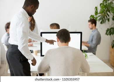 African American mentor helping Caucasian middle aged male employee to deal with computer software, using PC application, explaining operation processes, lecturing, teaching intern. Leadership concept