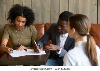 African American millennial couple sign mortgage contract meeting out in cafe with realtor, black lovers closing deal with architect or designer, consulting them in casual atmosphere in coffee shop.