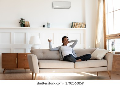 African american millennial girl, contented and calm, sit on comfortable sofa in cozy modern living room and hold remote control for the air conditioner. Enjoy cool fresh air in home