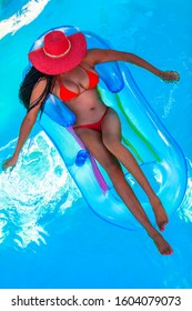 African American model in a bikini and red hat floats on an inflatable chair in a swimming pool.