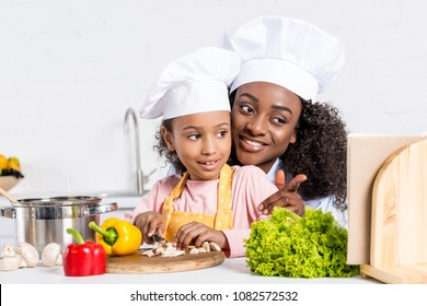 african american mother and daughter in chef hats cutting vegetables and looking into cookbook