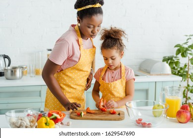 african american mother and daughter looking at bell pepper on cutting board